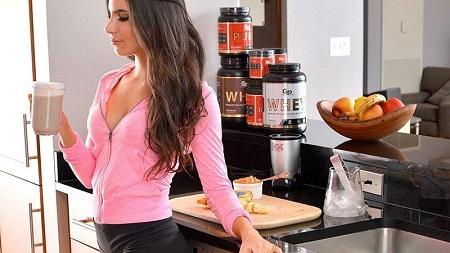 Mujer tomando proteínas después de entrenar