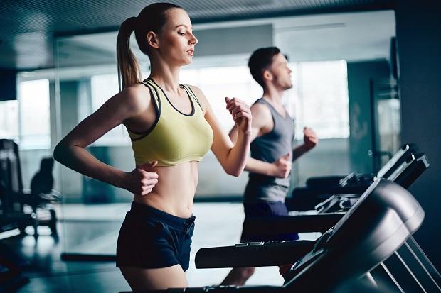 Mujer haciendo calentamiento muscular en cinta