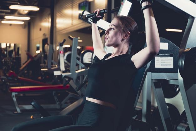 mujer entrenando sus hombros con maquina