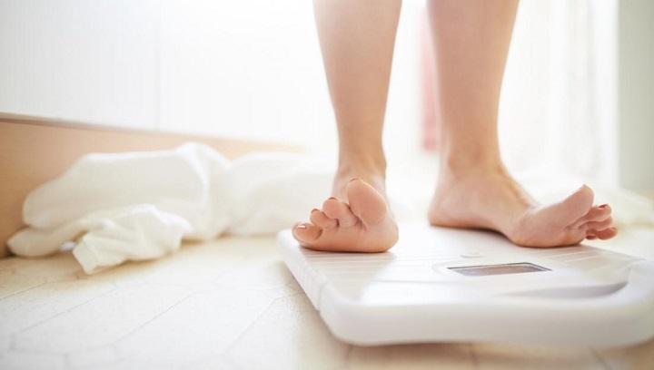 mujer sobre balanza controlando el efecto rebote
